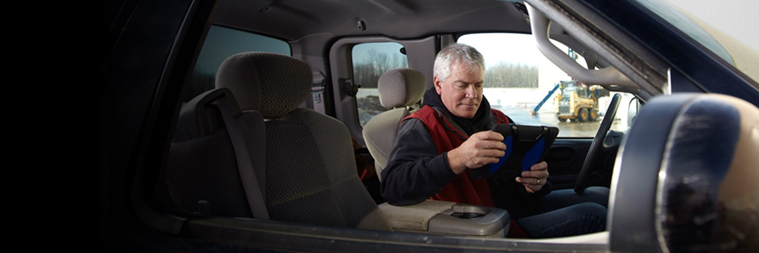 Man sitting inside truck reviewing tablet