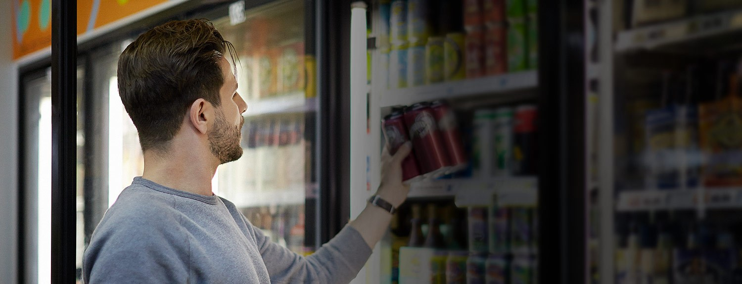 A male grabs a cold beverage from a convenience store refrigerator
