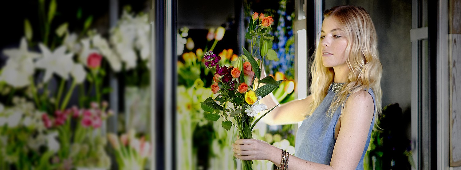 A beautiful flower shop owner prepares a bouquet. The store's refrigerators are powered by KOHLER generators.