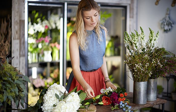 A beautiful flower shop owner arranges a bouquet of flowers