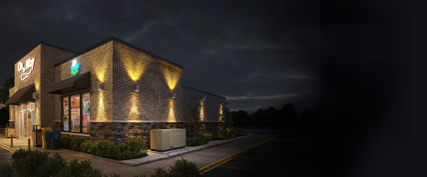A modern gas station/convenience store is lit up at night, powered by a KOHLER generator