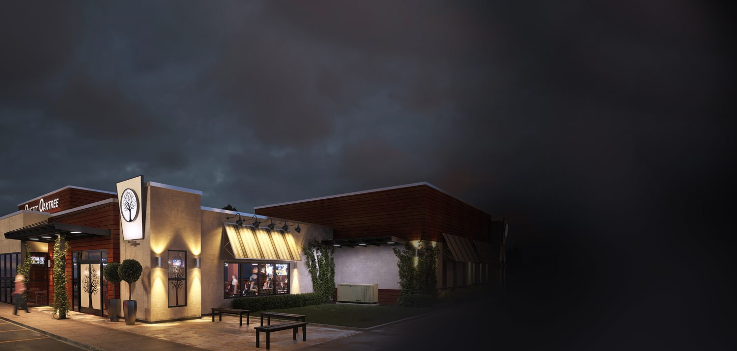 A modern restaurant is lit up against the night sky, powered by a KOHLER generator