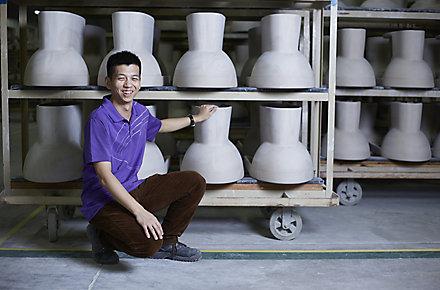 A Kohler Co. employee wearing a purple shirt kneels down to inspect racks of KOHLER toilets