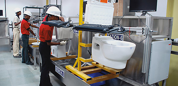 Three Kohler Co. employees work in a sustainability plant, testing toilets