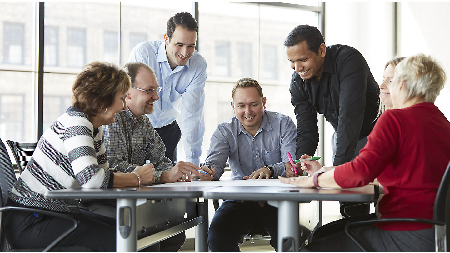 A team of six employees gathers around a table discussing ideas for Kohler Co., each wearing business casual attire