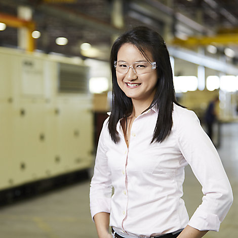 A woman in a dress shirt and safety glasses smiles at the camera in front of Kohler Co. manufacturing equipment