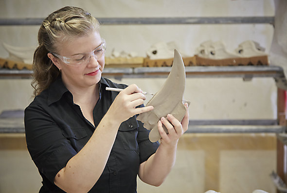 An artist in Kohler Co.'s Arts/Industry program uses a small tool to shape a clay sculpture