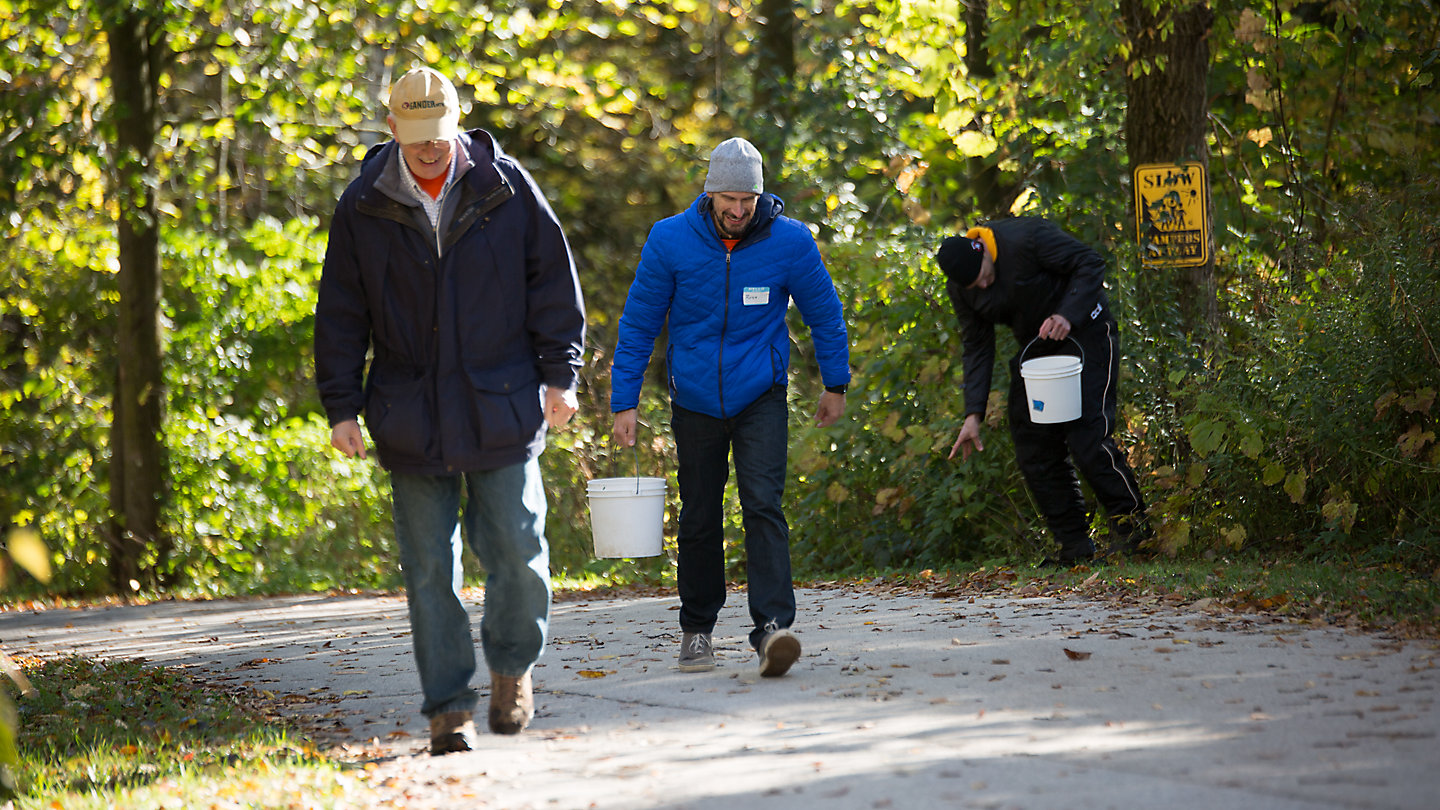Three Kohler Co. employees walk on an outdoor path carrying five-gallon buckets