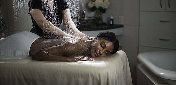 A woman lies on a massage table with a towel draped over her lower half. Water rains down on her as she's massaged by a Kohler Waters Spa employee