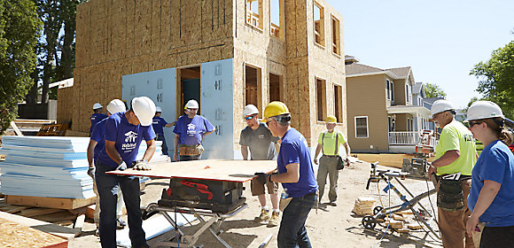 Kohler Power employees gather around a table saw in front of a partially finished home they are building in partnership with Habitat for Humanity