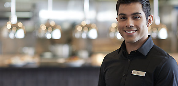 A man with a black polo shirt and name tag stands in the foreground while a Destination Kohler restaurant kitchen appears in soft focus behind him