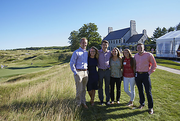 A group in the Supply Chain Rotational Program at Kohler Co. stands close together outside with Whistling Straits golf course in the background