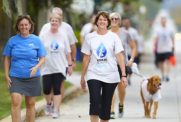People participate in a fundraiser event to support Kohler's Safe Water for All initiative. Most wear matching event t-shirts, and one women walks a dog.