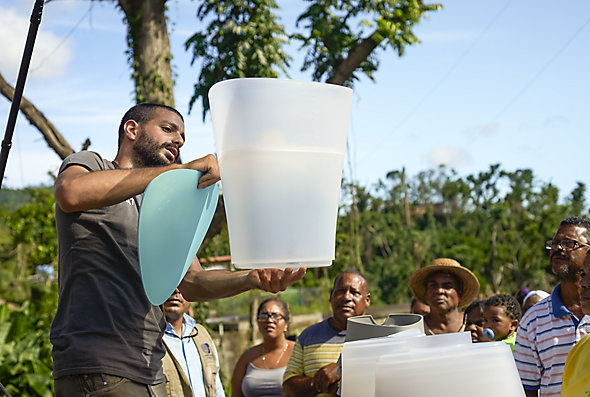 A man demonstrates how to use KOHLER® Clarity™ water filters to a group of people in Puerto Rico after the island was devastated by Hurricane Maria