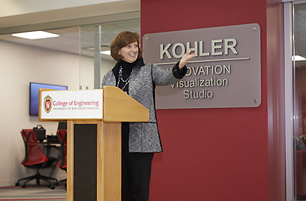 Cynthia Bachmann, Kohler Kitchen & Bath Vice President – Engineering and Product Development, stands behind a University of Wisconsin podium and in front of a Kohler Innovation Visualization Studio sign.