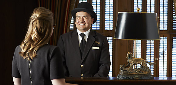 A man wearing a formal hat and suit greets a woman in a black dress in the lobby of The American Club hotel