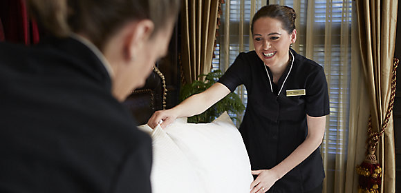 Two housekeepers in crisp, black dresses ensure the pillows are perfectly placed in a guest room at The American Club