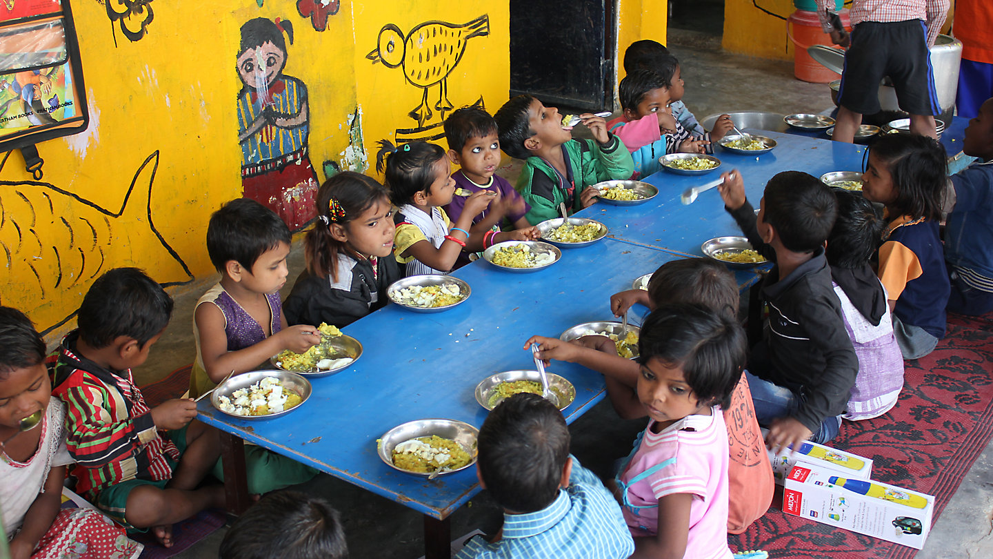 15 children sit around a big table eating with colorful paintings on the wall behind them