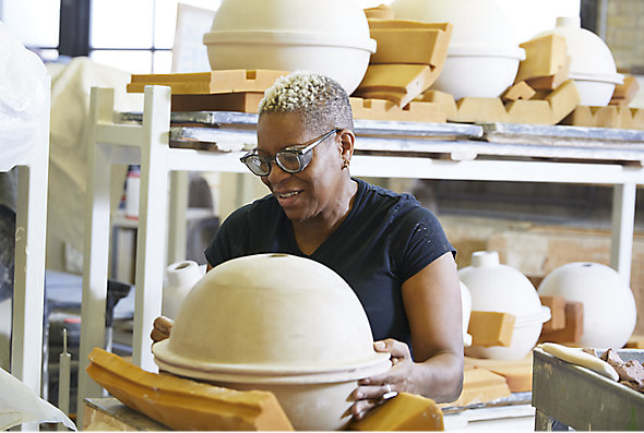 A woman sculpts a large clay piece of art in the Kohler Pottery, Iron and Brass Foundries, and Enamel Shop
