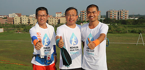 Three employees from the Kohler Co. plant in Foshan, China, stand outside together giving the thumbs-up symbol after completing a Kohler Run for Charity