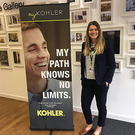 Cristina Bigica, Marketing and Communication – Buyer for Kohler Co. in Gloucester, UK, stands in front of a wall of framed artwork next to a sign that says My Path Knows No Limits