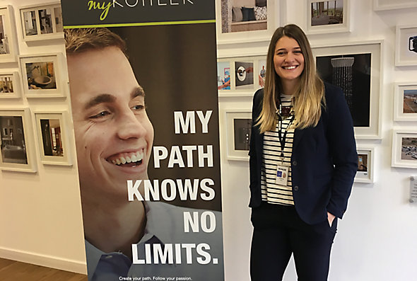 Cristina Bigica, Marketing and Communication – Buyer for Kohler Co., stands in front of a wall of framed artwork next to a sign.