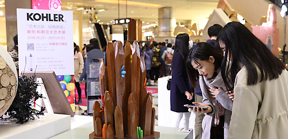 Amidst a busy background, two women look at a sculpture that's part of Multiculturalism, an exhibit from the Bold. Art. Program