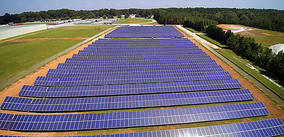 An aerial view of rows of solar panels next to a field, trees, and a factory