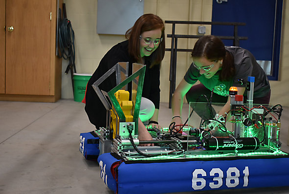 Engineer Megan Kennedy-Pierce and another Kohler Co. employee kneel on the floor by a robot they're helping build as volunteers of a Sheboygan-area robotics club