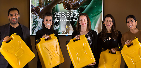 Five Kohler Mira employees stand side by side holding yellow water containers