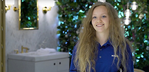 A woman in a blue polo shirt with Kohler logo smiles at the camera. A Kohler vanity and plants are in the background