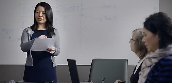 A woman who works in Finances at Kohler stands in front of a white board talking to two other employees