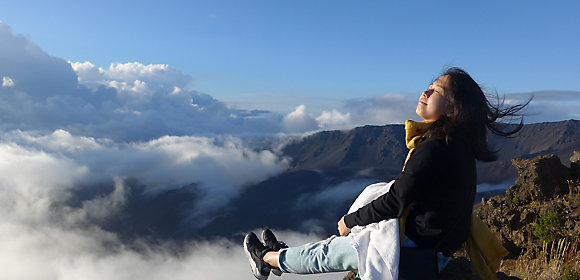 A Kohler intern sits at the edge of a cliff with a gorgeous view of mountains and clouds in the background
