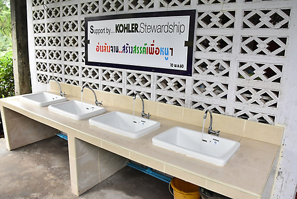 A row of four sinks in front of a sign that says Support by Kohler Stewardship