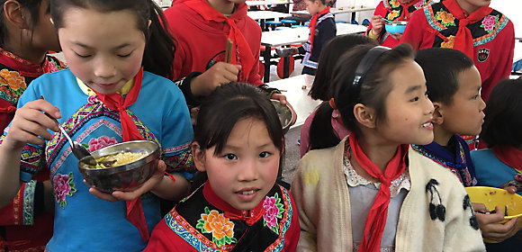 Kids eat at a school in rural China where Kohler China partners with CYDF to donate kitchen equipment, water filtration systems, faucets and sinks