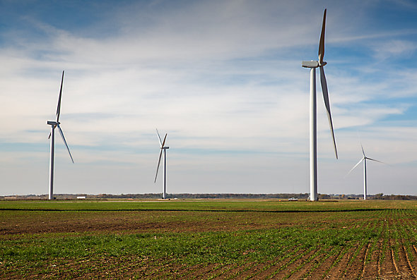 A broad landscape shot of windmills in farm fields with a truck driving by