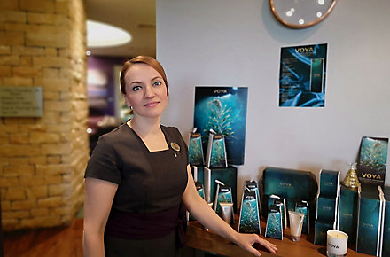 A woman wearing a black dress and name tag stands in the Kohler Water Spa at St Andrews, Scotland, with spa retail products in the background
