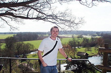 Dan Eaton, Procurement Manager – Professional Services at Kohler Co. stands on a balcony with beautiful green grass, trees, and creek behind him