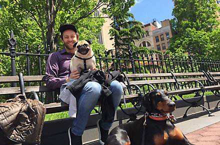 Seth Stevens, Chief Designer, Decorative Products, for Kohler Co. in Kohler, Wisconsin, sits on a park bench with one dog on his lap and another in front of him