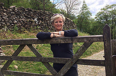 Linda Waite, NPD Project Leader for Kohler Co. in Cheltenham, England, stands behind a fence with her arms crossed. A stone wall and trees are in the background