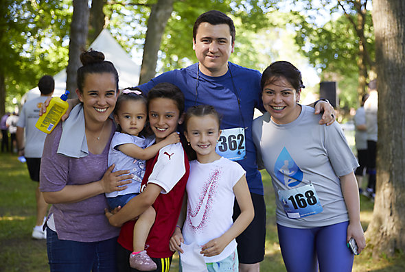 A family gathers with their arms around each other as the father, a Kohler Co. employee, and one child have just finished a fundraising run or walk together