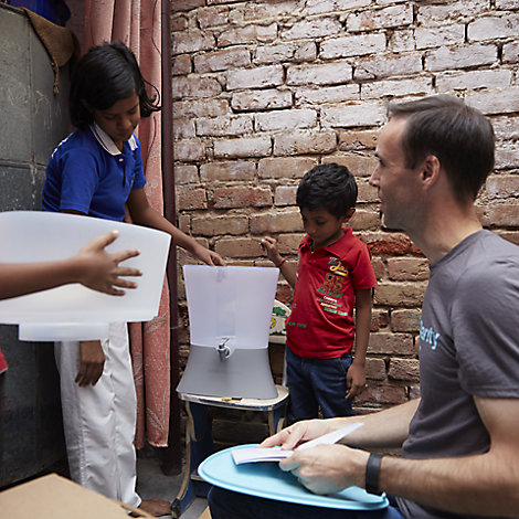 Two kids inspect a KOHLER Clarity water filter as an adult looks on