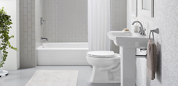 A white and gray bathroom with a KOHLER pedestal sink, toilet, bath, and faucets