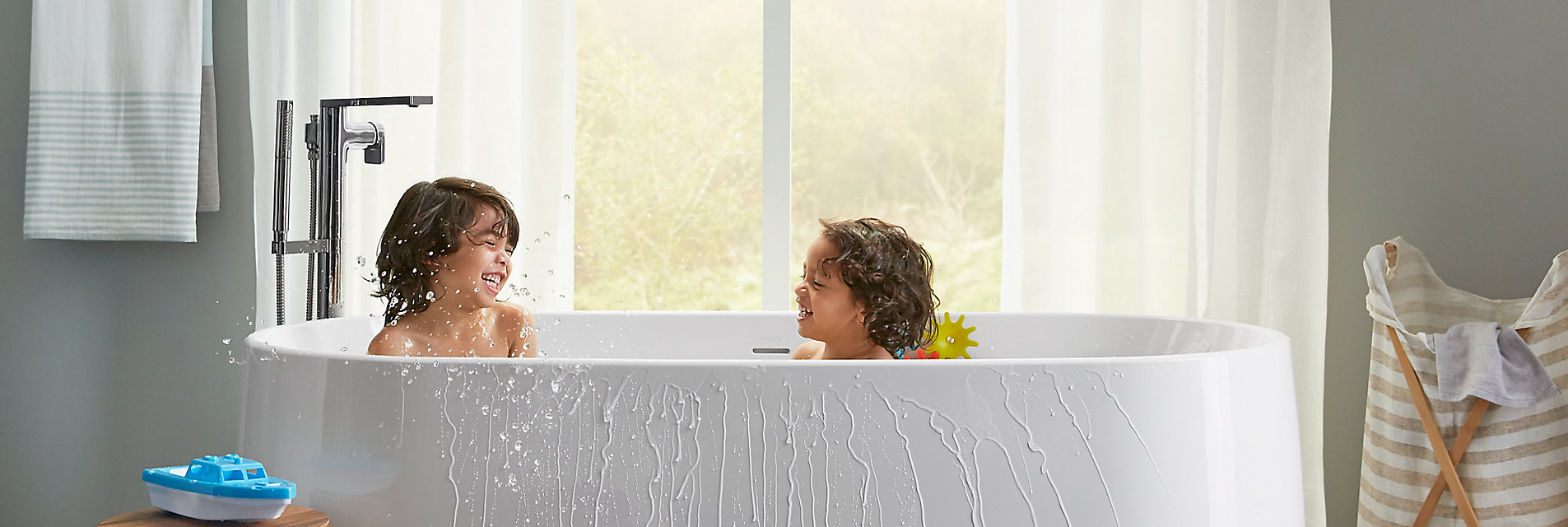 Two kids splash in a bath.